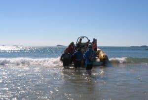 Passengers boarding Venture Jet jet boat at Whitesands beach St Davids Pembrokeshire
